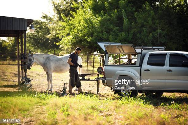 Side view of farrier making horseshoe while standing on grassy field by pick-up truck