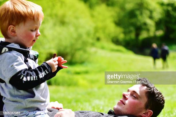 side view of father and boy in park - malton stock pictures, royalty-free photos & images