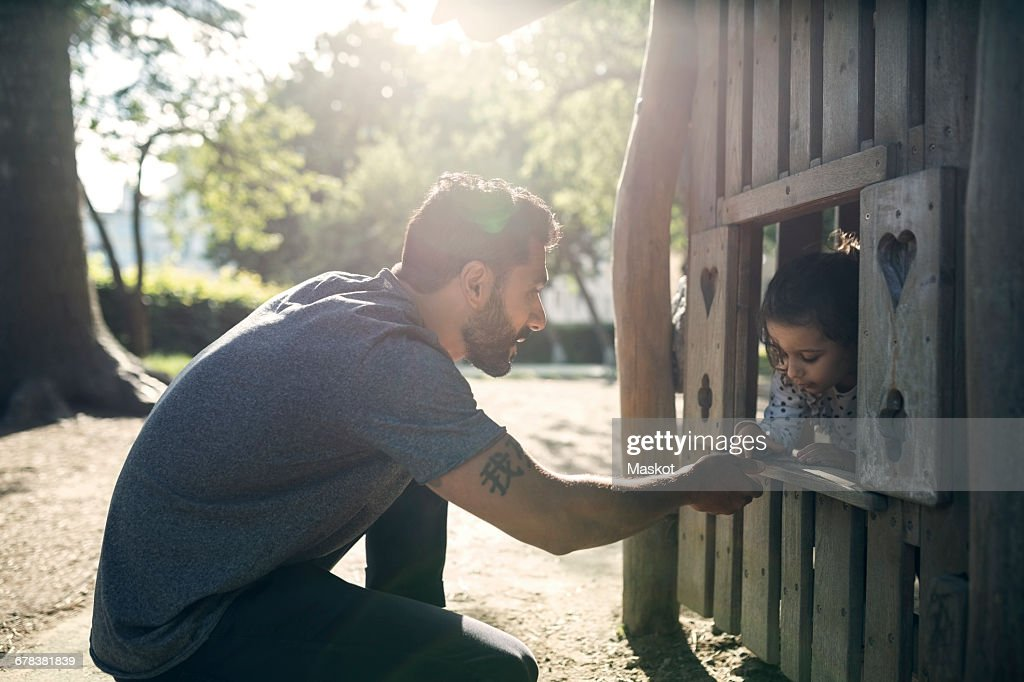 Side view of father and daughter playing in wooden toy house : Stock Photo
