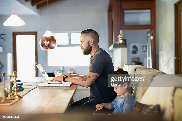 Side view of father and son using technologies at dining table