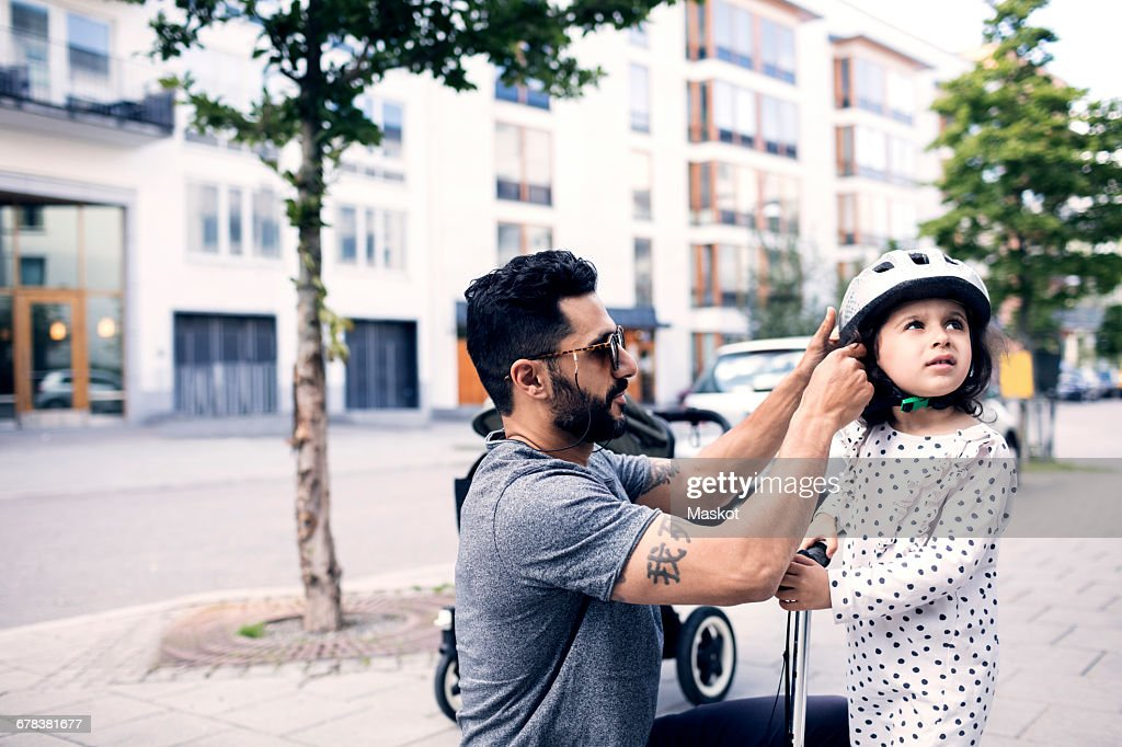 Side view of father assisting daughter in wearing helmet at sidewalk : Stock Photo