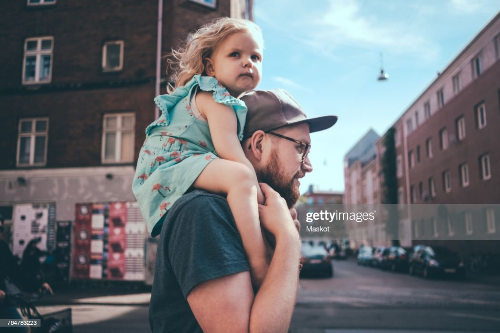 Side view of father carrying daughter on shoulders at city street : Stock Photo
