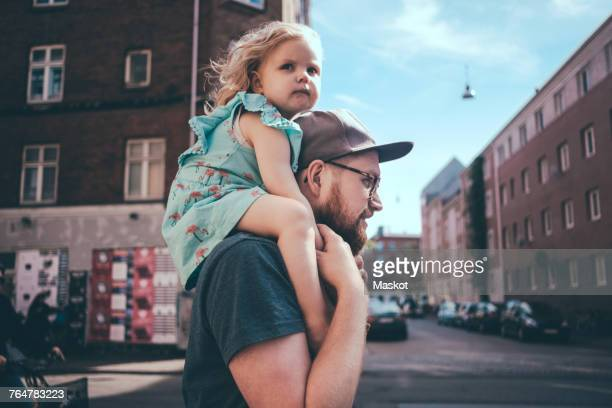 Side view of father carrying daughter on shoulders at city street
