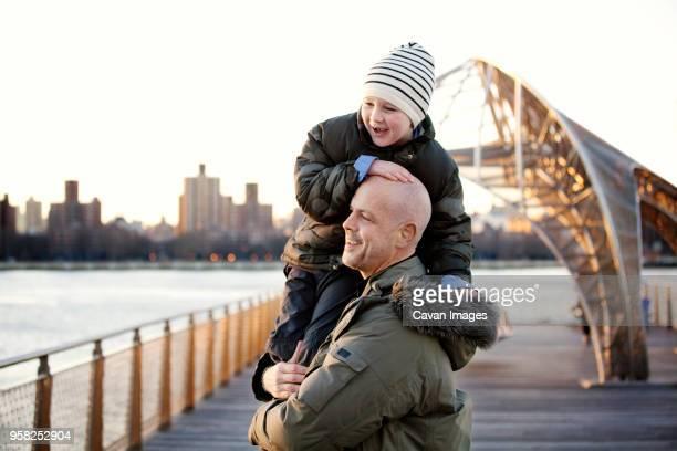 side view of father carrying son - careca imagens e fotografias de stock