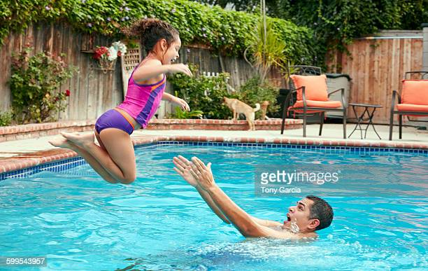 Side view of father catching girl jumping into swimming pool, in mid air