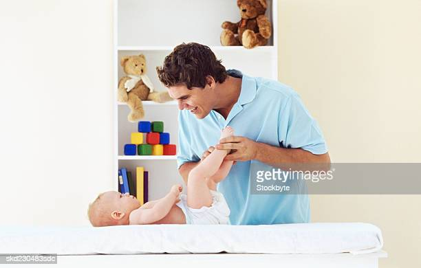 Side view of father changing baby boy's nappy (6-12 months)