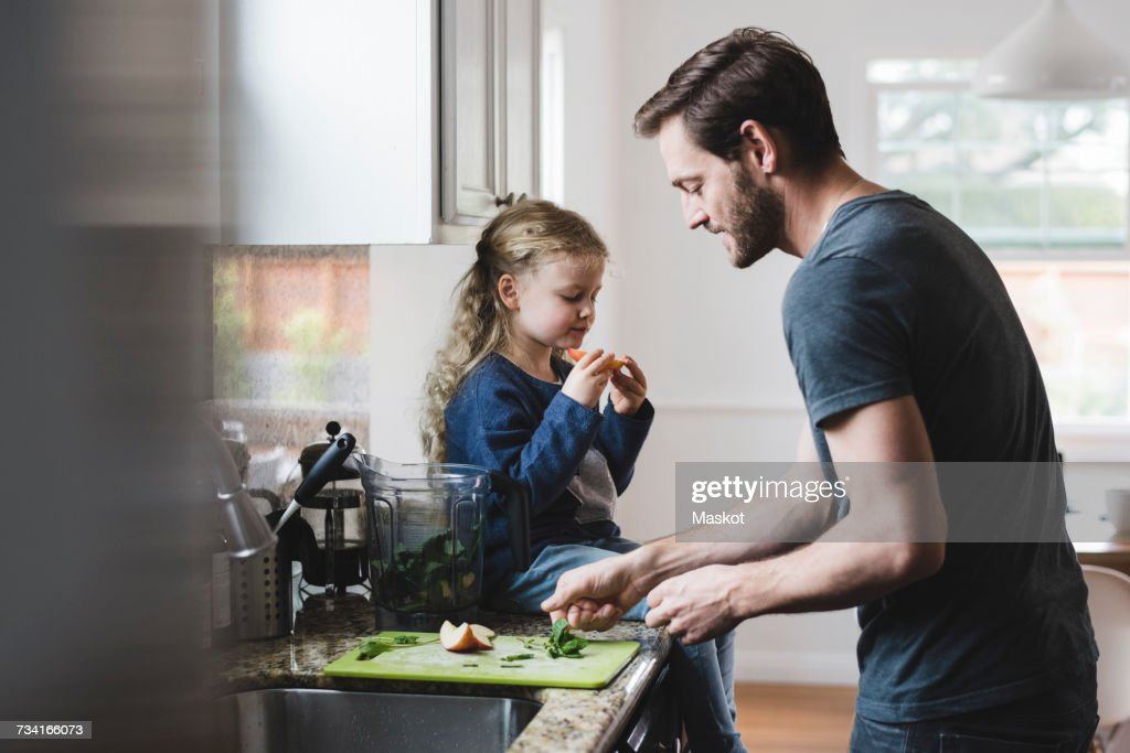 Side view of father cooking food while daughter having apple in kitchen : Stock Photo