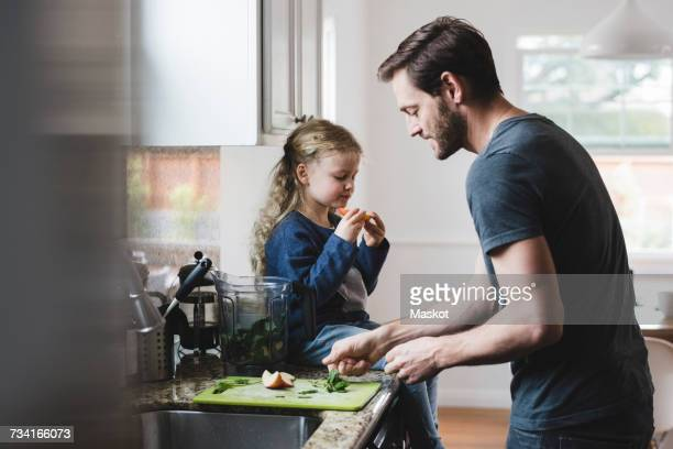 side view of father cooking food while daughter having apple in kitchen - one parent stock pictures, royalty-free photos & images