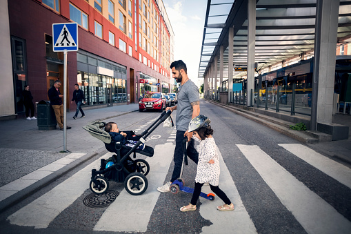 Side view of father crossing street with daughter while holding baby stroller in city - gettyimageskorea