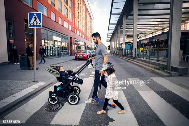 side view of father crossing street with daughter while holding baby stroller in city - pedestrian crossing stock photos and pictures