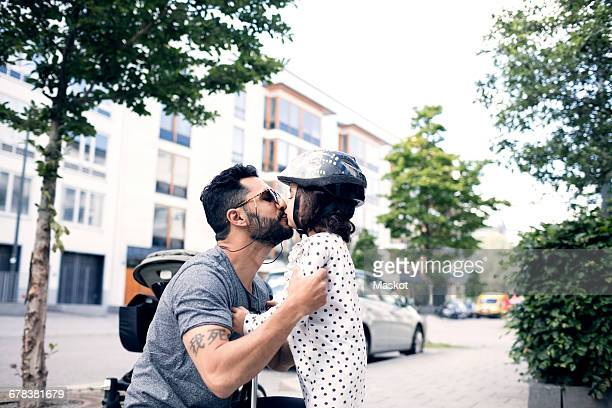 Side view of father kissing daughter while crouching on sidewalk
