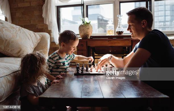 side view of father playing chess with children on table at home - playing chess stock pictures, royalty-free photos & images