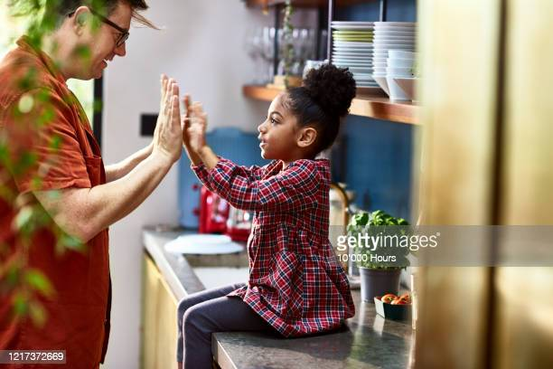side view of father playing pat a cake with daughter - genderblend stock pictures, royalty-free photos & images