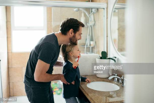 Side view of father watching daughter brushing teeth at sink in bathroom