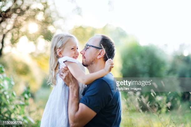 A side view of father with a cheerful toddler daughter outdoors in nature in summer.
