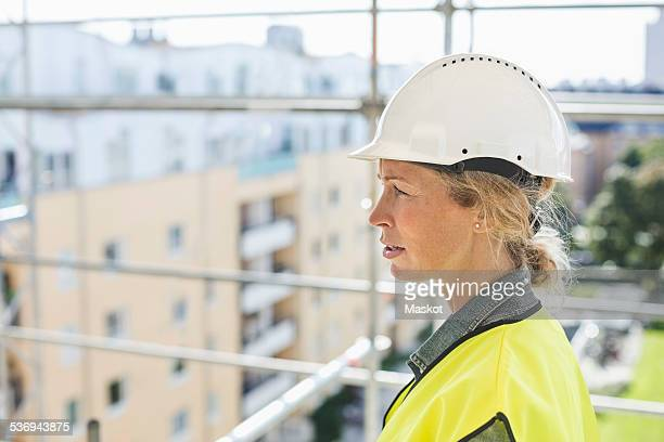 Side view of female architect at construction site