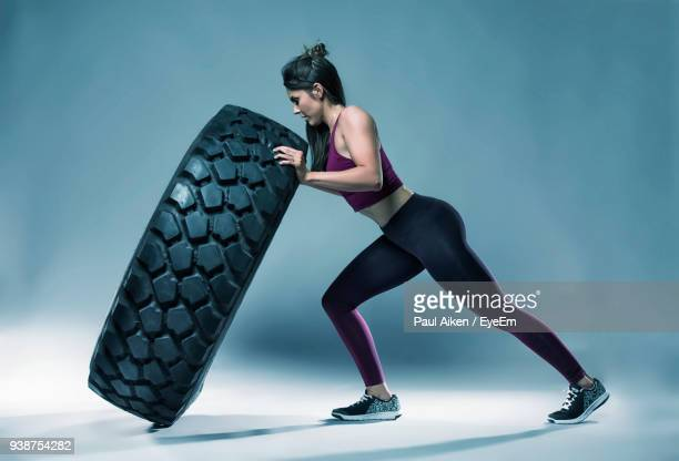 side view of female athlete pushing tire over gray backdrop - aikāne stock pictures, royalty-free photos & images