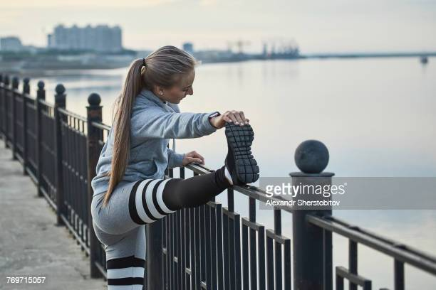 Side view of female athlete stretching by railing on footpath, Blagoveshchensk, Amur, Russia