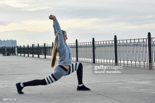 Side view of female athlete stretching on promenade
