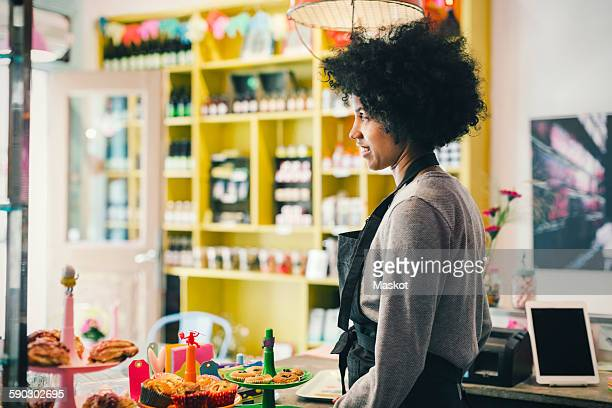 Side view of female barista standing at cafe counter