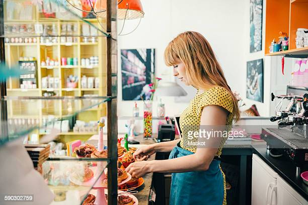 Side view of female barista with pastries at cafe counter