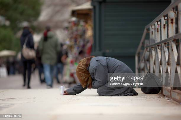 side view of female beggar begging on footpath in city - sandra gygax stock-fotos und bilder