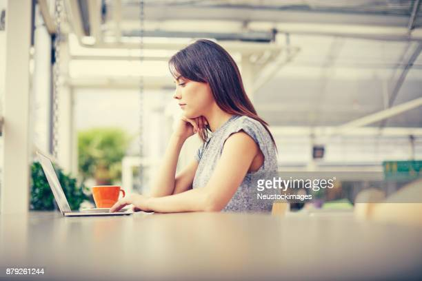 Side view of female blogger using laptop at table in cafe