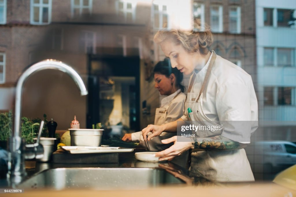 Side view of female chefs preparing food at counter in restaurant kitchen seen from window : Stock Photo