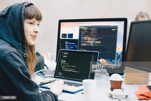 Side view of female computer programmer looking away while using laptop at desk in office
