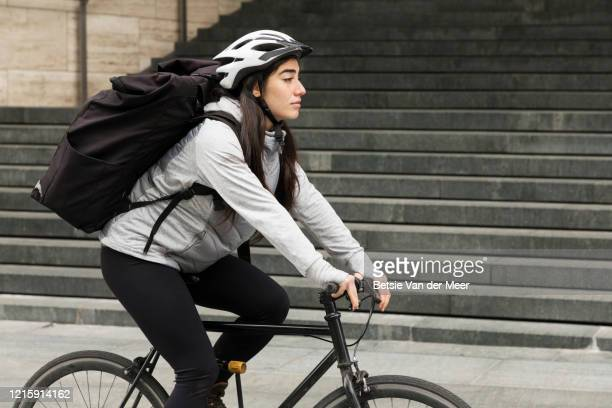 side view of female courier cycling in city street. - helmet stock pictures, royalty-free photos & images