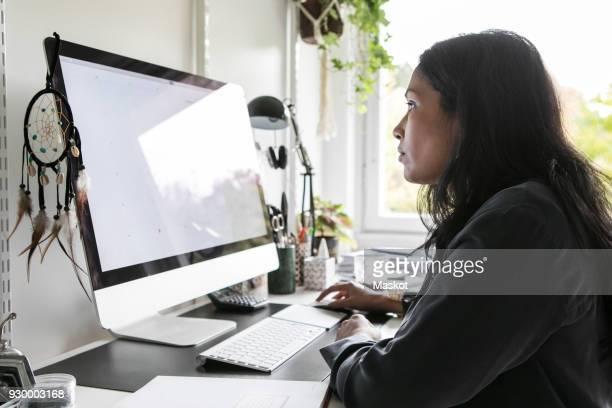 Side view of female design professional using computer while sitting in home office
