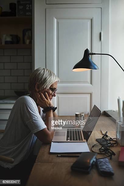 Side view of female designer working late at home office