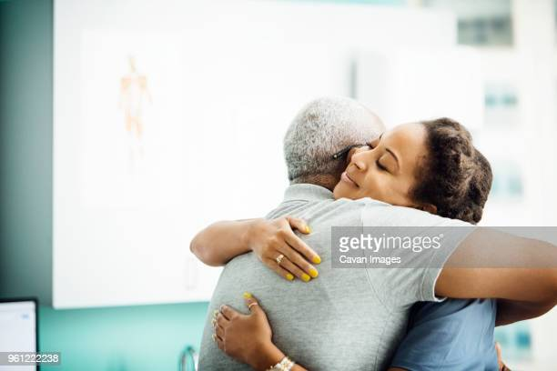 Side view of female doctor embracing senior male patient in clinic