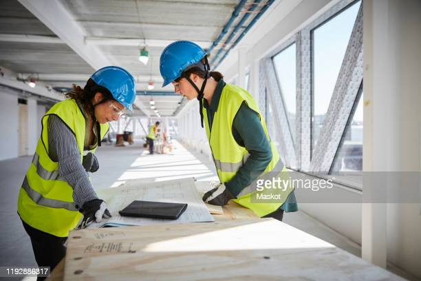 side view of female engineers discussing over blueprint at construction site - hearing protection stock pictures, royalty-free photos & images
