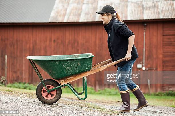 side view of female farmer pushing wheelbarrow on rural road - wheelbarrow stock photos and pictures