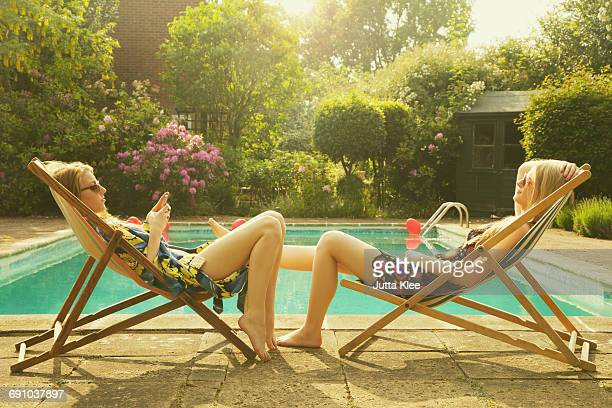 side view of female friends relaxing on deck chairs at poolside during summer - transat photos et images de collection