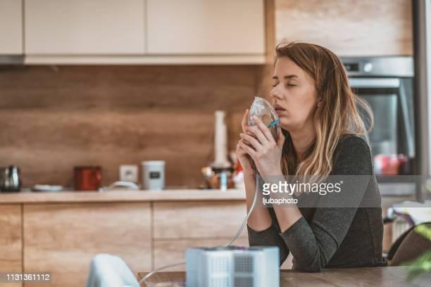 side view of female holds a mask vapor inhaler - amigdalite imagens e fotografias de stock