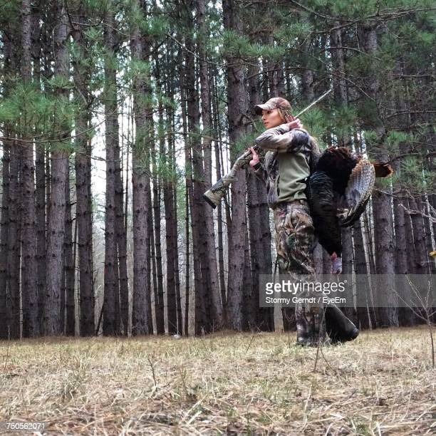 side view of female hunter with dead turkey bird at forest - turkey hunting stock photos and pictures
