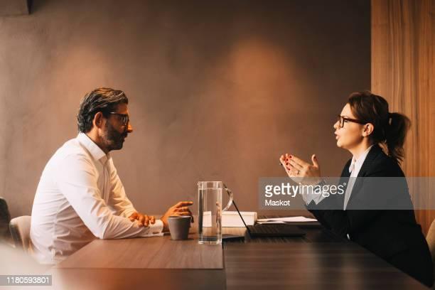 side view of female lawyer explaining mature client in meeting at office - finanzen und wirtschaft stock-fotos und bilder
