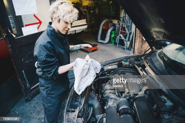 Side view of female mechanic checking oil with dipstick outside auto repair shop