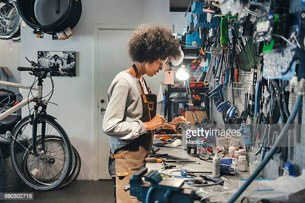 Side view of female mechanic working in bicycle workshop