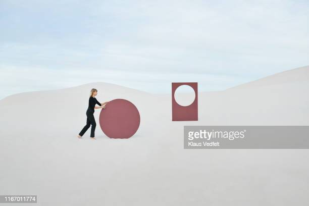 side view of female model pushing circular portal at white desert against sky - concept stock pictures, royalty-free photos & images