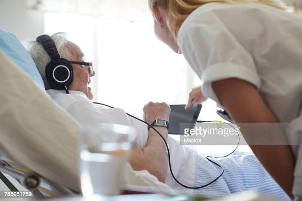 Side view of female nurse assisting senior man in using digital tablet on hospital bed