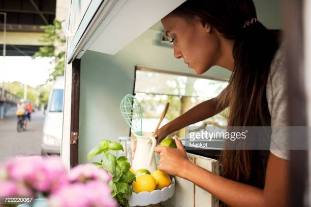Side view of female owner holding lemon while working in food truck