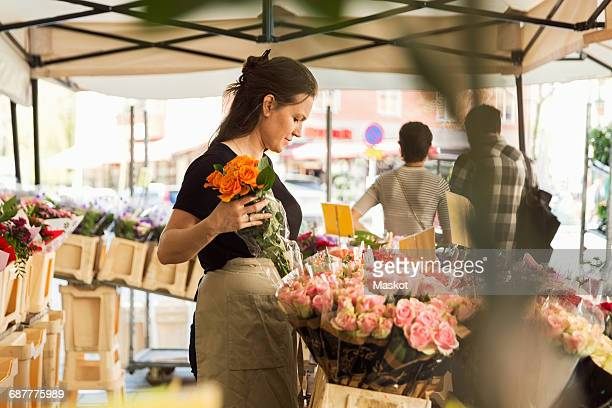 Side view of female owner working at flower shop
