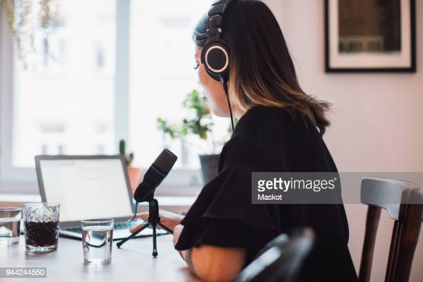 side view of female podcaster wearing headphones sitting at table with microphone at home - vlogging stock photos and pictures