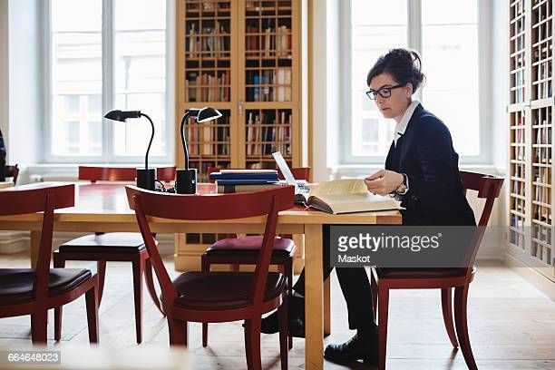Side view of female professional reading book at table in law library