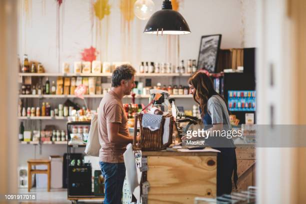 side view of female sales clerk with customer at checkout counter in deli - geschäftsinhaber stock-fotos und bilder