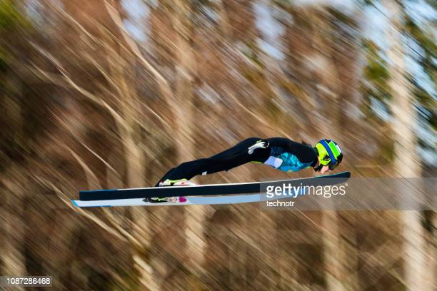 Side View of Female Ski Jumper in Mid-air Against Blurred Background