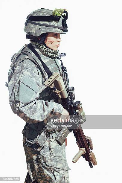 Side view of female soldier carrying rifle while standing against white background